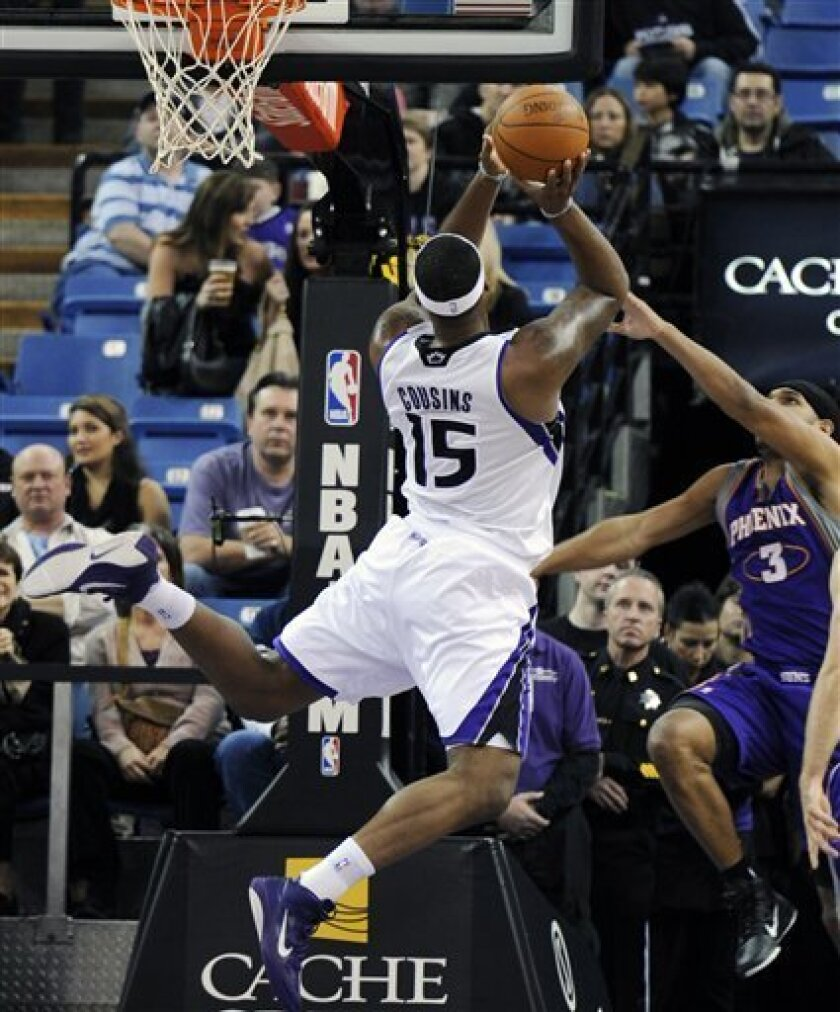 Sacramento Kings center DeMarcus Cousins (15) gets a shot off and is fouled by Phoenix Suns' Jared Dudley (3) in the first half of an NBA basketball game in Sacramento, Calif., Sunday, Jan. 2, 2011. (AP Photo/Thearon Henderson)
