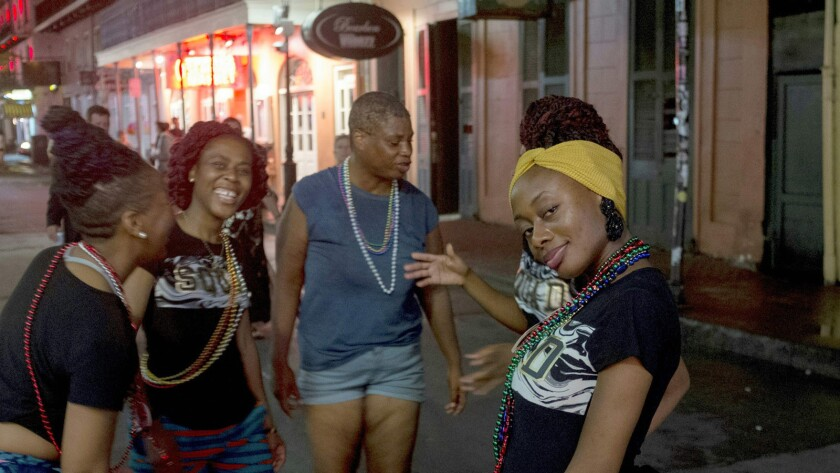 People mingle on Bourbon Street in New Orleans ahead of the storm Friday night.