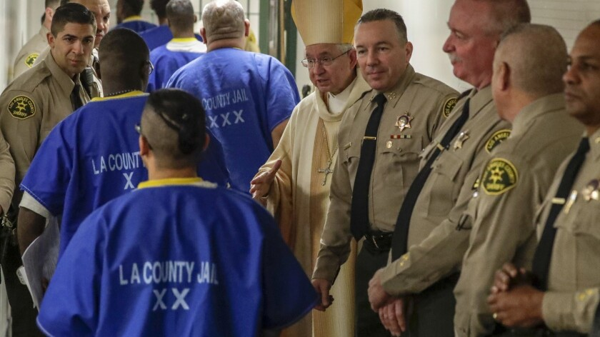 Archbishop Jose H. Gomez, center, and new L.A. County Sheriff Alex Villanueva, fourth from right, greet inmates after a Christmas Mass at Men's Central Jail.