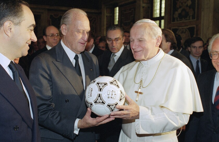 Joao Havelange, center, presents Pope John Paul II with a soccer ball during a visit to Vatican City in 1989