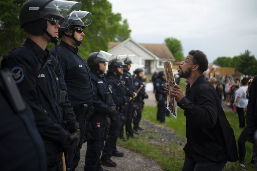 A demonstrator holding a sign jumps up and down so police officers behind the front lines could see it, outside the Oakdale, Minn,, home of fired Minneapolis police Officer Derek Chauvin on Wednesday evening, May 27, 2020.