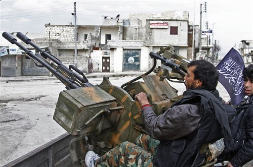 In this Friday February 8, 2013, photo, Free Syrian Army fighters sit behind their anti-aircraft weapon in Aleppo, Syria. Syrian rebels brought their fight within a mile of the heart of Damascus on Friday, seizing army checkpoints and cutting a key highway with a row of burning tires as they presse