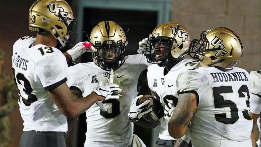 Central Florida's Alex Swenson (30) is congratulated on his touchdown by teammates Dredrick Snelson