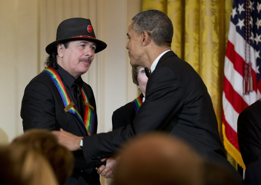 President Barack Obama, right, congratulates 2013 Kennedy Center Honors recipient Carlos Santana, during a reception honoring the 2013 Kennedy Center Honors recipients, in the East Room of the White House in Washington D.C. on Sunday, Dec. 8, 2013.