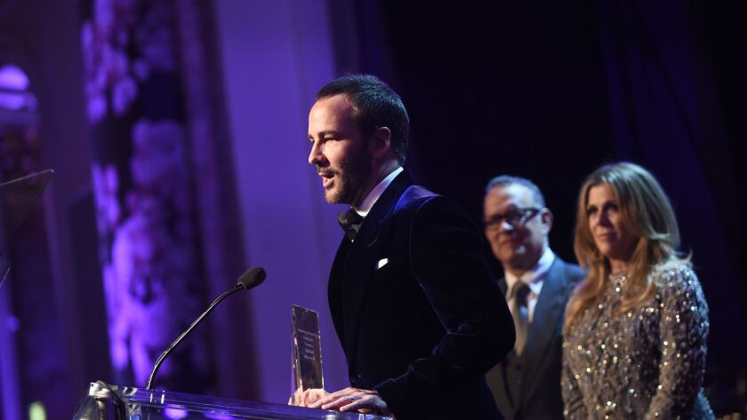 Tom Ford accepts the Courage Award from honorary co-chairs Rita Wilson and Tom Hanks during the Women's Cancer Research Foundation's An Unforgettable Evening on Feb. 16.