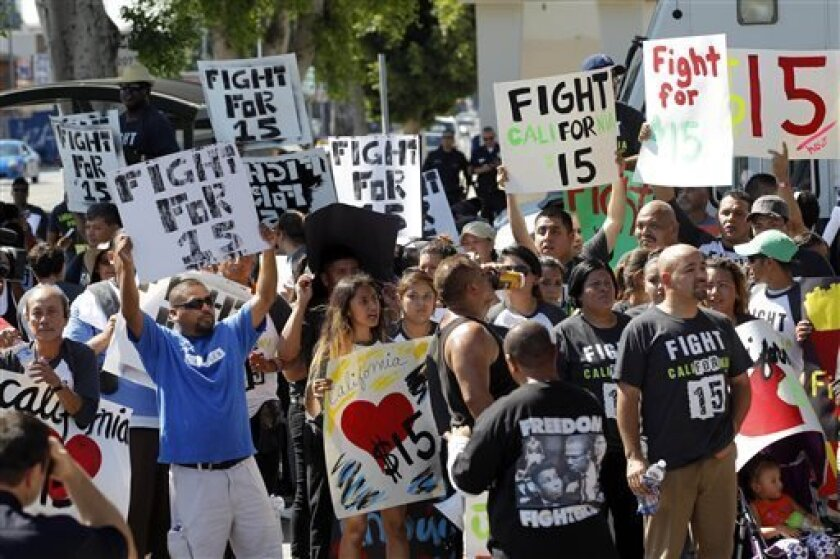 FILE - In this Aug. 29, 2013, file photo, protestors demonstrate outside a fast-food restaurant in Los Angeles. Thousands of fast-food workers and their supporters have been staging protests across the country to call attention to the struggles of living on or close to the federal minimum wage. The