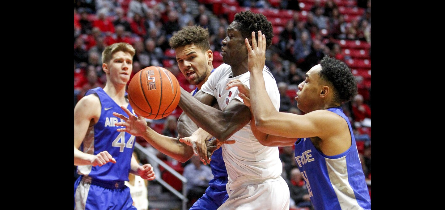 The Aztecs' Nathan Mensah, center, grabs a rebound while in between Air Force's Ryan Swan, left, and A.J. Walker during the first half.