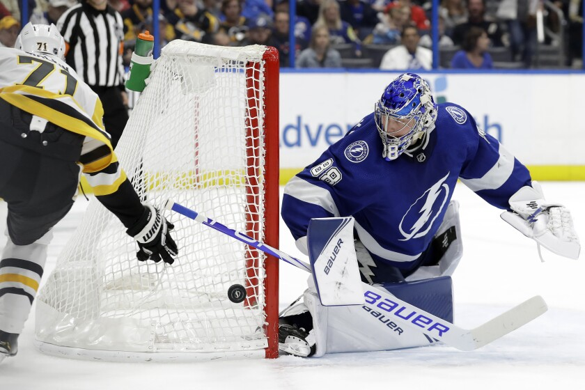 Tampa Bay Lightning goaltender Andrei Vasilevskiy (88) makes a save on a shot attempt by Pittsburgh Penguins center Evgeni Malkin (71) during the first period of an NHL hockey game Thursday, Feb. 6, 2020, in Tampa, Fla. (AP Photo/Chris O'Meara)