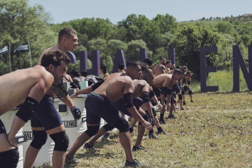 A line of men in matching black athletic shorts and knee pads preparing to start a race