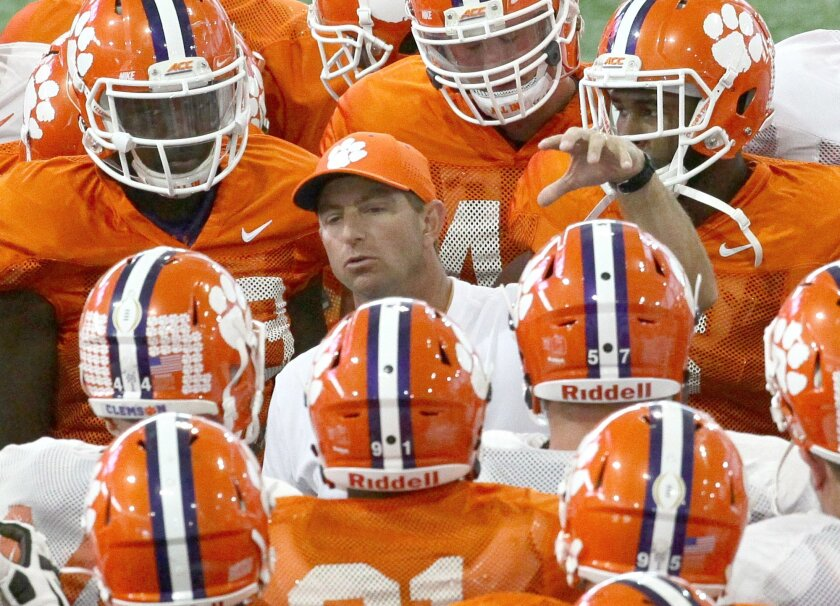 Clemson head coach Dabo Swinney, center, talks to his players. He makes millions of dollars a year. His players are forbidden from even acting as coaches in the offseason.