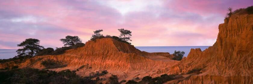 Pastel hues create a serene mood as the sun rises at Broken Hills Overlook in Torrey Pines State Natural Reserve near La Jolla, California