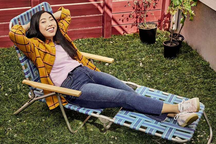 Awkwafina reclines on a lawn chair.