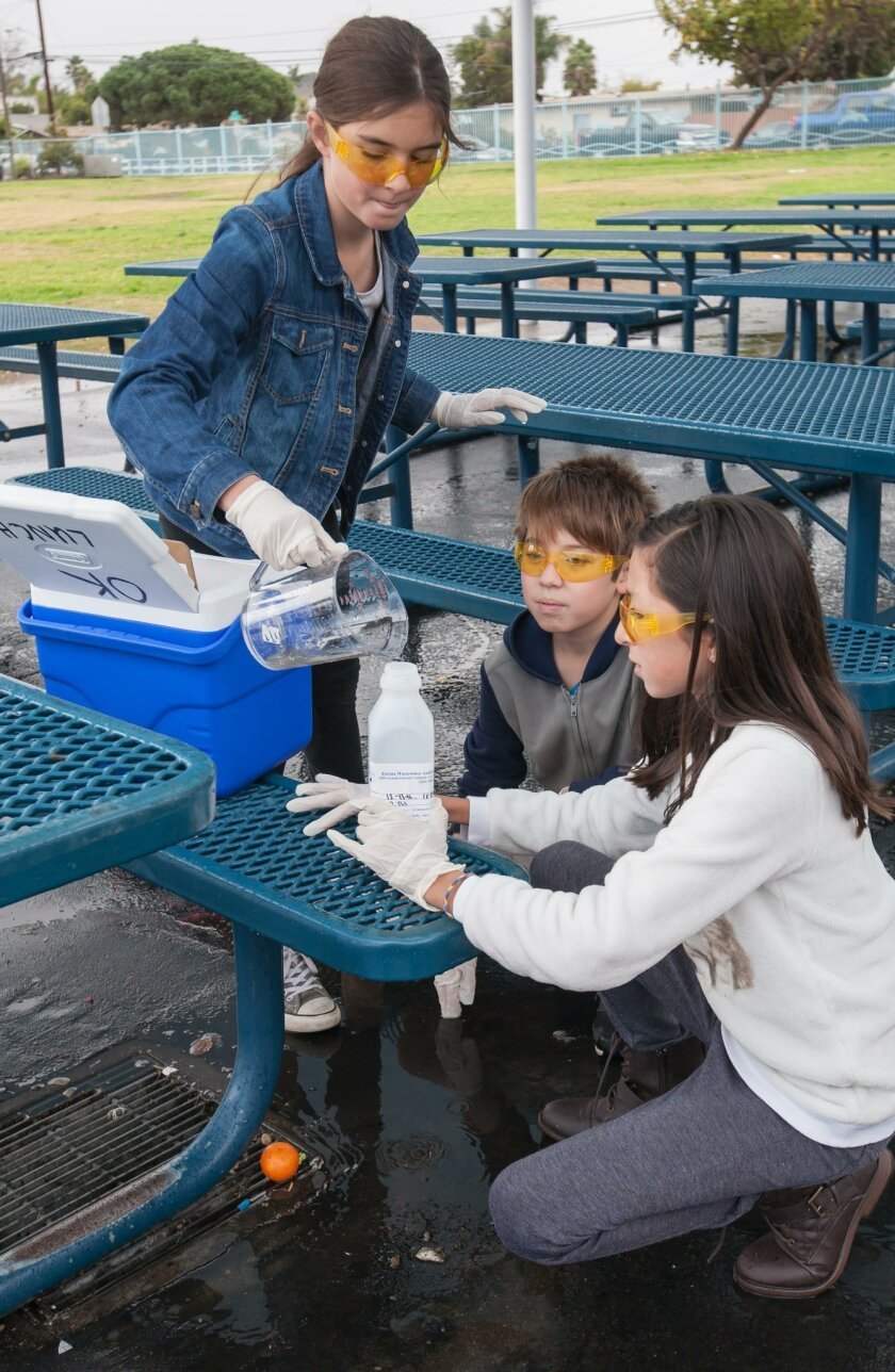 Ocean Knoll students — from left, Ellyanna Cinzori, Reese Goldboss and Camilla Rodriguez — collect a rain event sample at the lunch drain as part of the award-winning Stormwater Pollution Prevention Program (SWPPP).