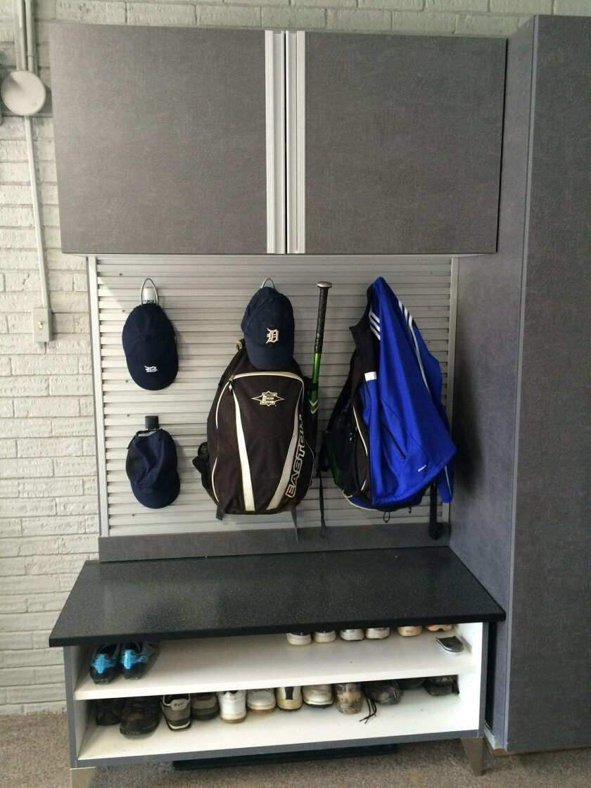 In this photo provided by Tailored Living/Premier Garage, Todd Carter of Tailored Living featuring Premier Garage decided to clean up the a messy garage space to make it more attractive and useful. Carter added wall storage systems and flooring to transform the space into a workout room. One area i
