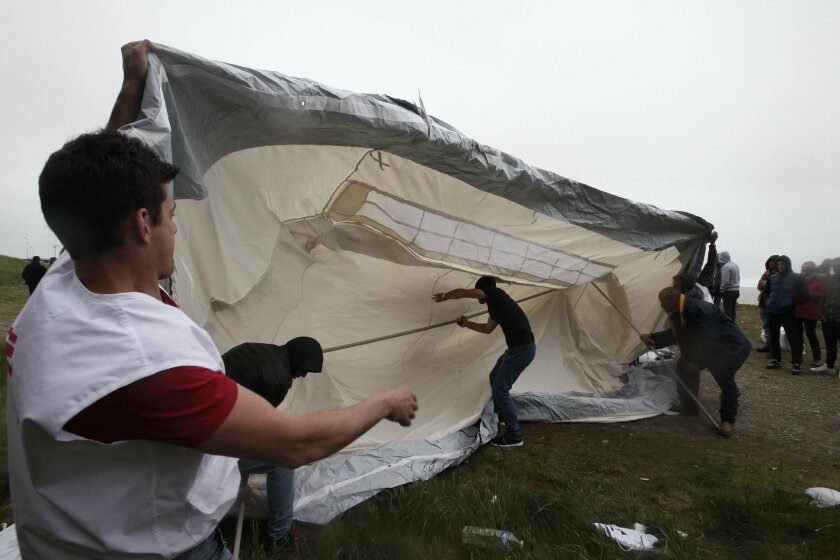 A member of the international medical charity, left, known by its French acronym MSF in a new makeshift camp along the storm-hit cliffs near the port of Dieppe, northern France, Wednesday, June 1, 2016. A group of around 150 Albanian migrants set up camp near the English channel hoping to cross to