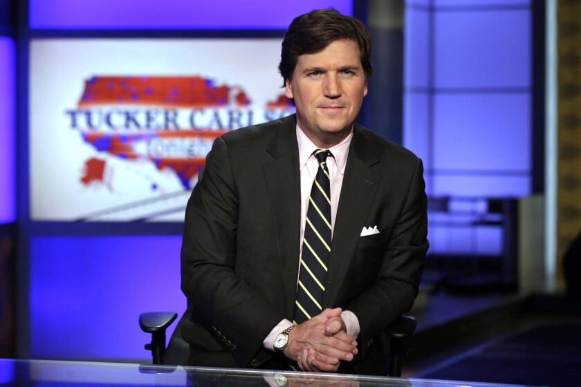 "FILE - In this March 2, 2017 file photo, Tucker Carlson, host of ""Tucker Carlson Tonight,"" poses for photos in a Fox News Channel studio, in New York. Tucker Carlson's top writer has resigned from Fox News after secretly posting racists and sexist remarks online. CNN reported Friday, July 10, 2020 that writer Blake Neff used a pseudonym to write bigoted comments about Black and Asian people, as well as women, on the online platform AutoAdmit.(AP Photo/Richard Drew, File)"