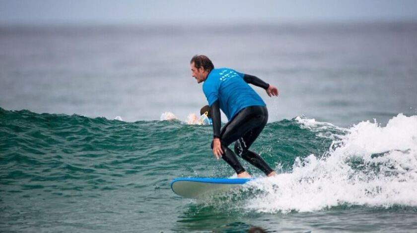 Shaun Tomson catches a wave in a past 100 Wave Challenge.