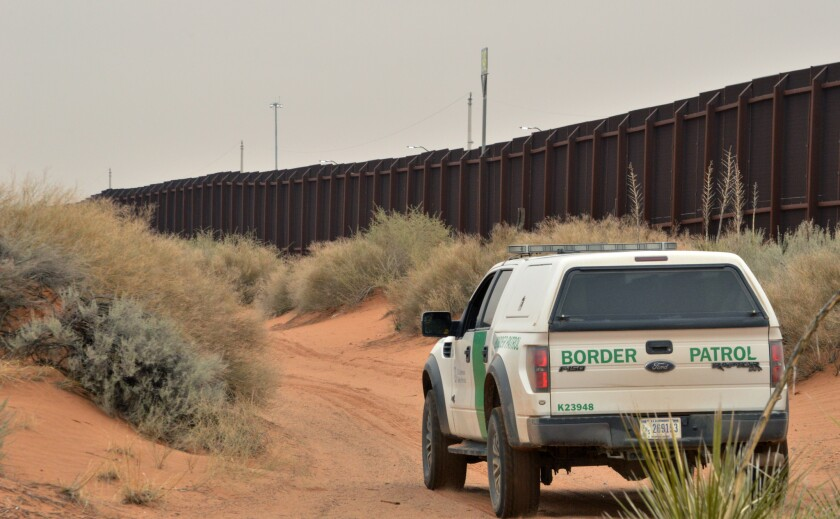 A Border Patrol agent drives near the U.S.-Mexico border fence in Santa Teresa, N.M.