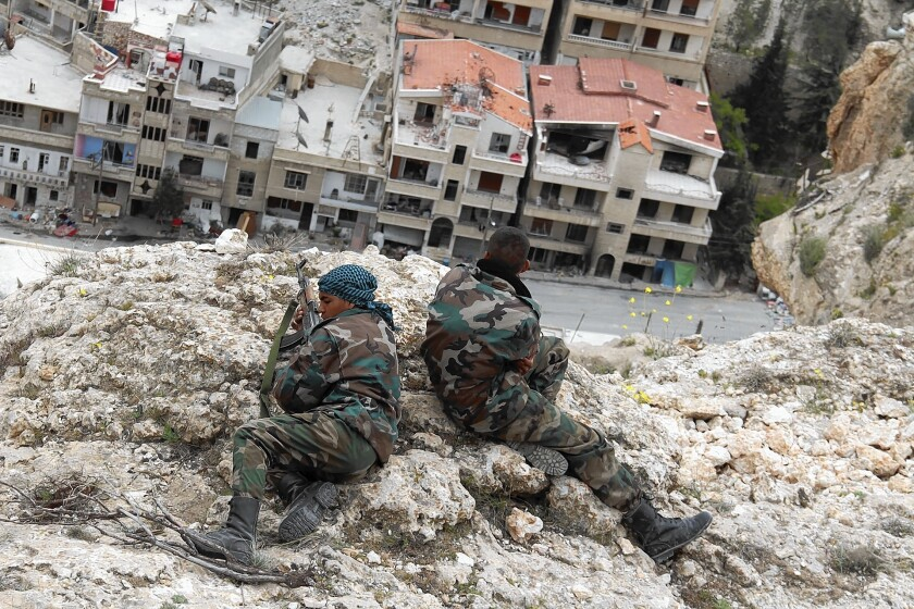 Fighters scan the streets below for any sign of rebels in Maaloula, Syria, where units of the Syrian army, pro-government militiamen and a loyalist Shiite militia have taken over.