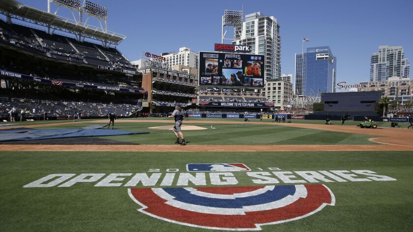 Groundkeepers prepare the field before an opening day baseball game between the San Diego Padres and the Milwaukee Brewers in San Diego, Thursday, March 29, 2018.