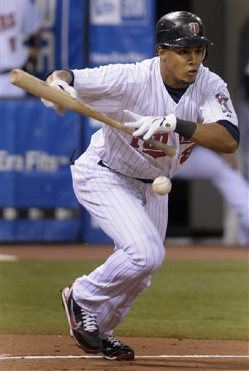 Minnesota Twins' Carlos Gomez bunts for a single during the first inning off Kansas City Royals starting pitcher John bale during a baseball game, Friday, April 4, 2008, in Minneapolis.(AP Photo/Tom Olmscheid)