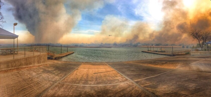 A fire that started in Arizona has jumped the Colorado River and is spreading toward Pirate's Cove in California.