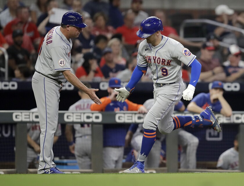 New York Mets' Brandon Nimmo, right, celebrates with third base coach Gary Disarcina after hitting a home run off Atlanta Braves' Spencer Strider in the seventh inning of a baseball game Friday, Oct. 1, 2021, in Atlanta. (AP Photo/Ben Margot)