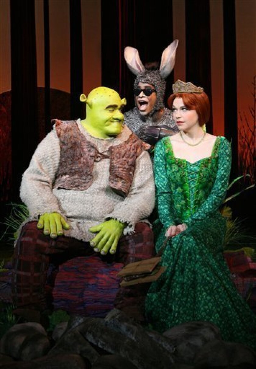 """In this image released by Boneau/Bryan-Brown, Brian d'Arcy James is shown as the title character of Shrek, left, with Daniel Breaker as Donkey and Sutton Foster as Princess Fiona in """"Shrek the Musical,"""" now playing at the Broadway Theatre in New York. (AP Photo/Boneau/Bryan-Brown, Joan Marcus)"""
