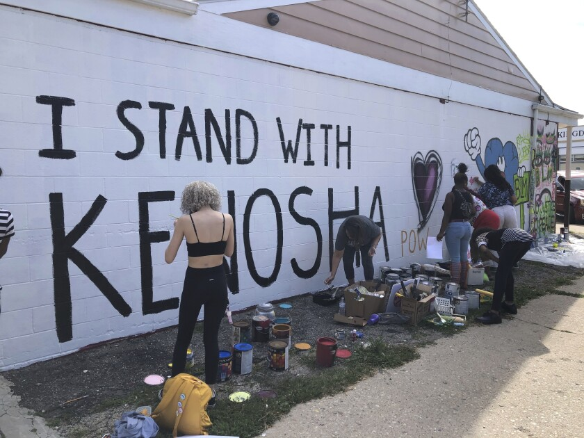 Volunteers paint murals on boarded-up businesses in Kenosha, Wis., on Aug. 30, 2020.