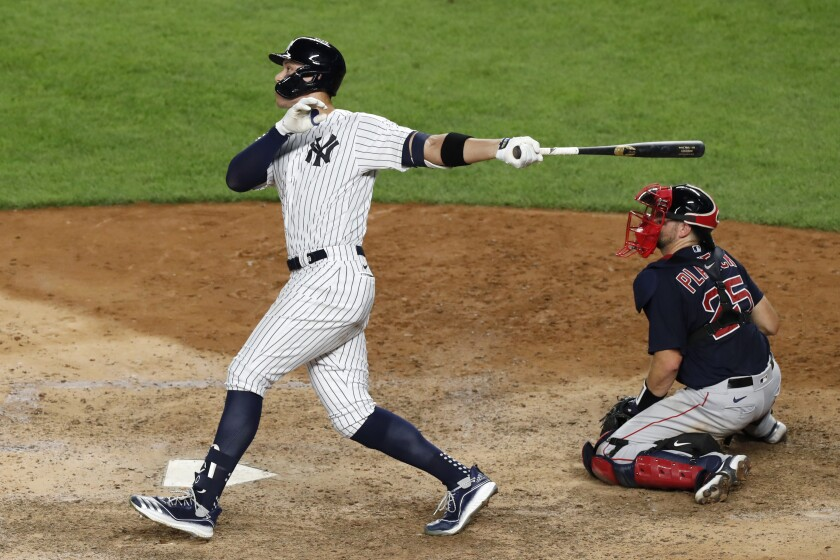 New York Yankees' Aaron Judge follows through on an eighth-inning, two-run home run against the Boston Red Sox in a baseball game Sunday, Aug. 2, 2020, at Yankee Stadium in New York. Red Sox catcher Kevin Plawecki is at right. (AP Photo/Kathy Willens)