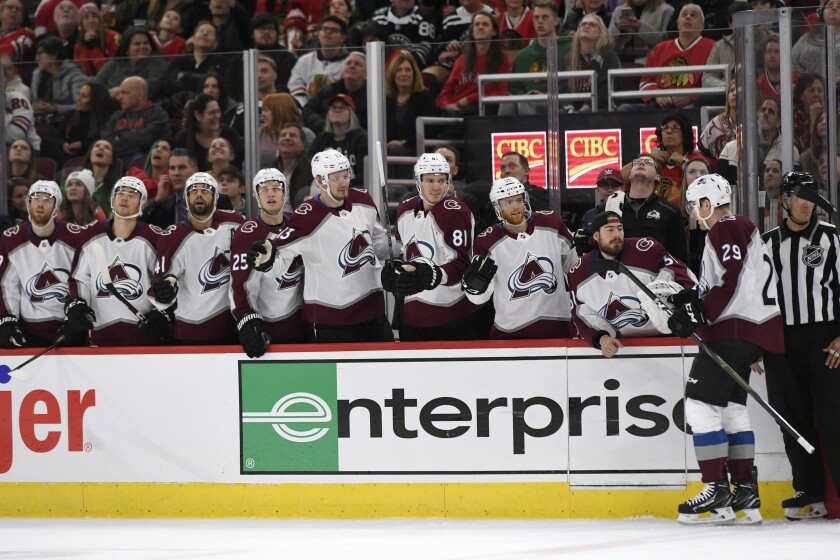Colorado Avalanche Nathan MacKinnon (29) celebrates with teammates on the bench after scoring during the first period of an NHL hockey game against the Chicago Blackhawks Friday, Nov. 29, 2019, in Chicago. (AP Photo/Paul Beaty)