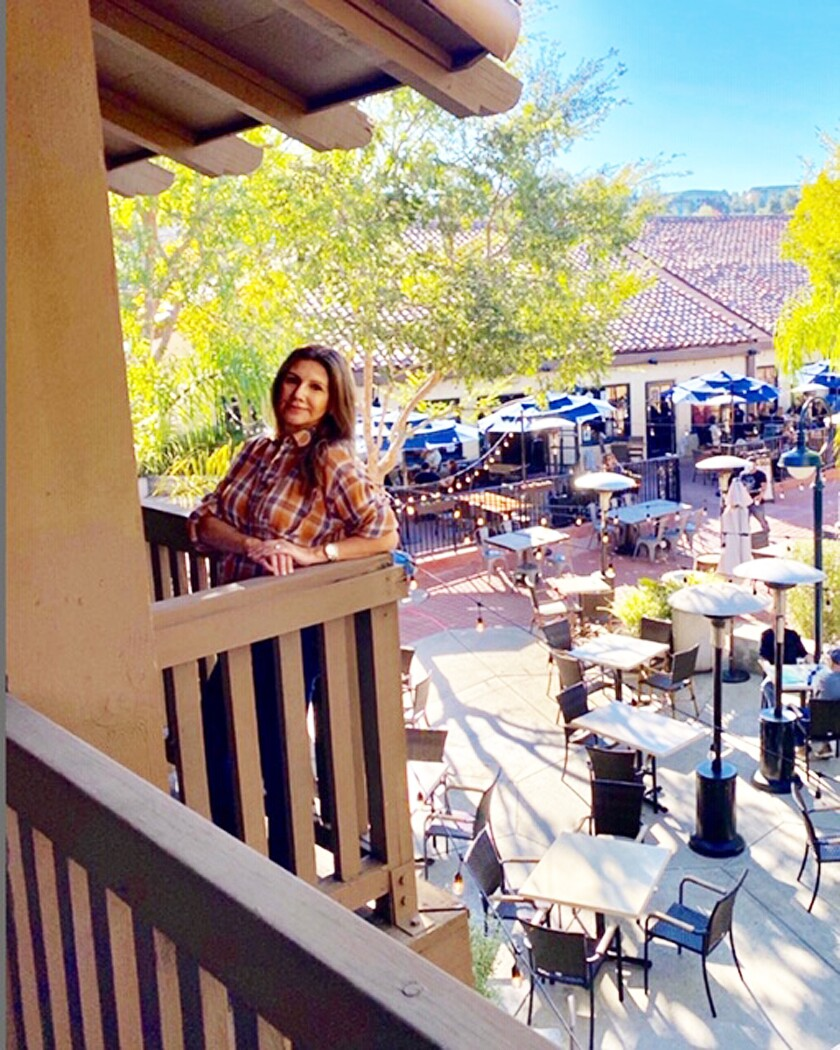 Senior Property Manager Cristina Sanchez in front of the The Plaza Rancho Bernardo's outdoor dining courtyard.