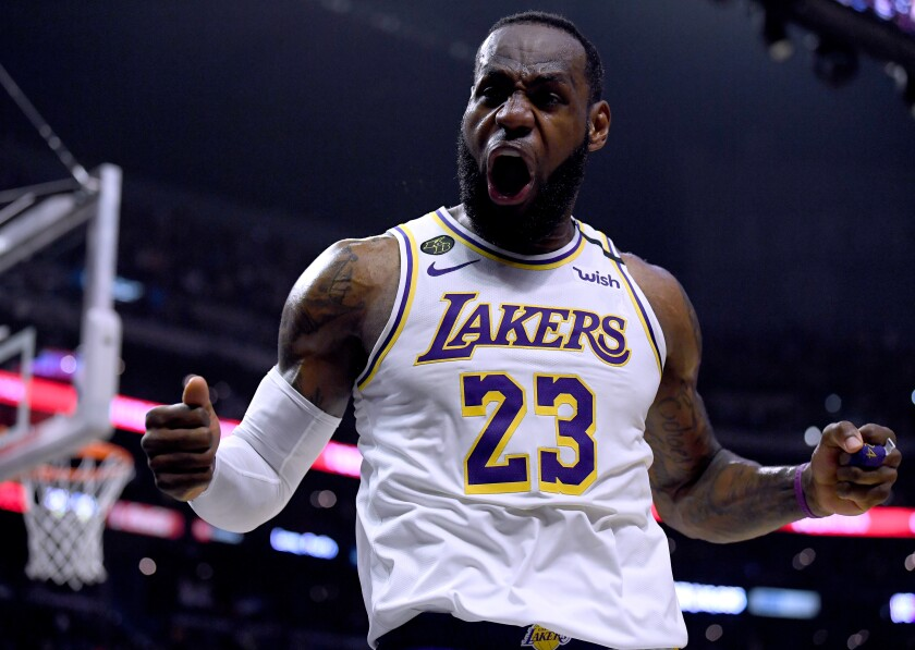 Lakers star LeBron James celebrates after scoring and drawing a foul during a 112-103 victory over the Clippers at Staples Center on Sunday.