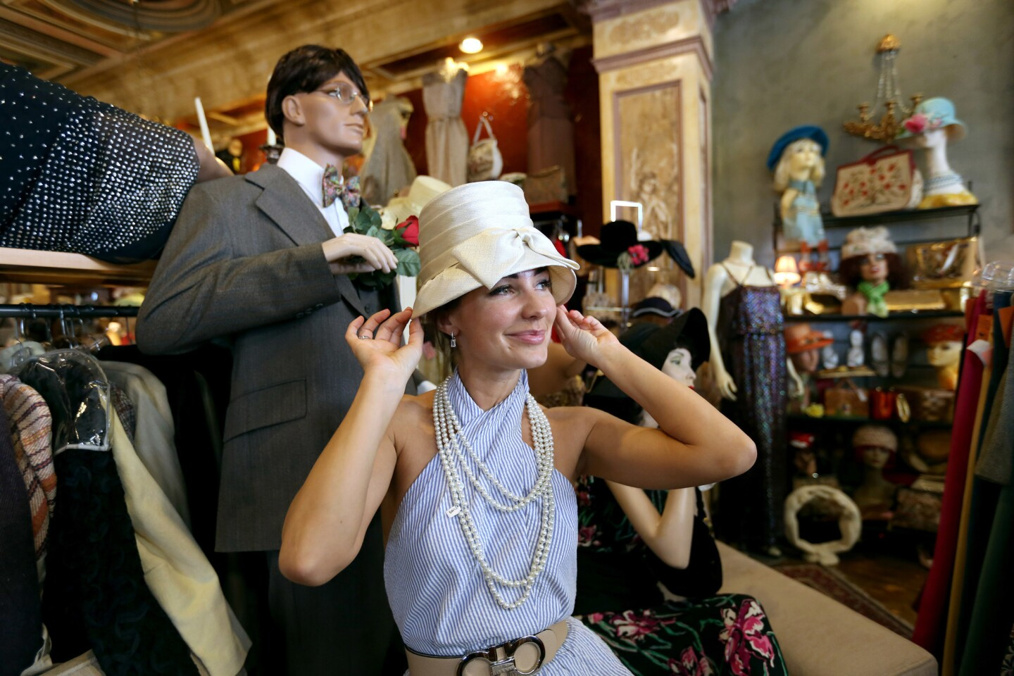 Alex Wilson, 35 of Los Angeles, tries on a vintage hat at Playclothes Vintage, in Burbank.