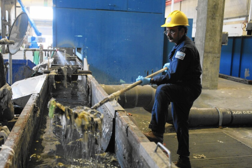 A worker at L.A.'s Hyperion sewage treatment facility removes trash that has been separated from incoming wastewater.