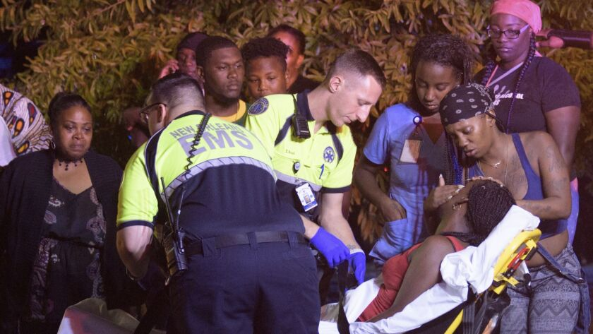 Emergency workers tend to a person that fainted near the scene of a shooting in New Orleans, Saturday night, July 28, 2018.