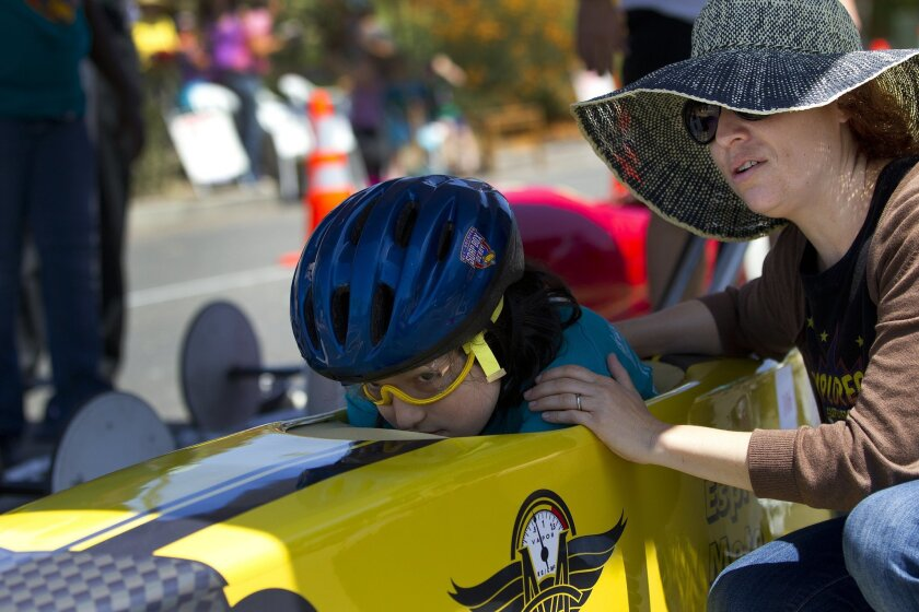On the start ramp, driver Aidan Tarral gets last minute race course advice from his mother Tasi Paulson just before the start of his stock division heat in the All-American Soap Box Derby.