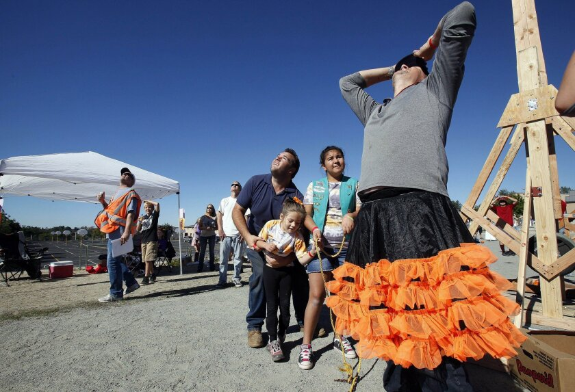 Joe Chaffee (in tutu) and others watch a pumpkin gain altitude at Sunday's Punkin' Chunkin' competition in Alpine.