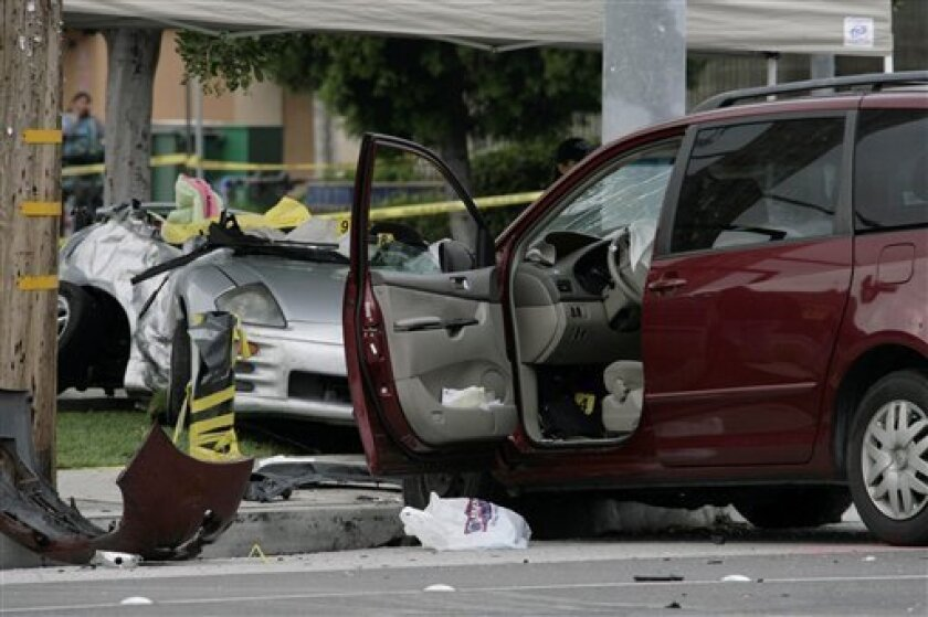 The red minivan, right, that hit the sports car of Los Angeles Angels rookie pitcher Nick Adenhart is shown at the scene of the hit-and-run car accident Thursday, April 9, 2009, in Fullerton, Calif. The accident that claimed the life of Adenhart and two other people. (AP Photo/Nick Ut)