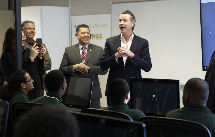 FILE - In this Jan. 22, 2019 file photo, Gov. Gavin Newsom, right, addresses youthful offenders taking a computer coding class at the O.H. Close Youth Correctional Facility in Stockton, Calif. Newsom is now considering legislation sent to him by lawmakers that would phase out the state-operated juvenile prison system, create an Office of Youth and Community Restoration and send grants to counties to provide custody and supervision of the most violent criminal youths. (AP Photo/Rich Pedroncelli, File)