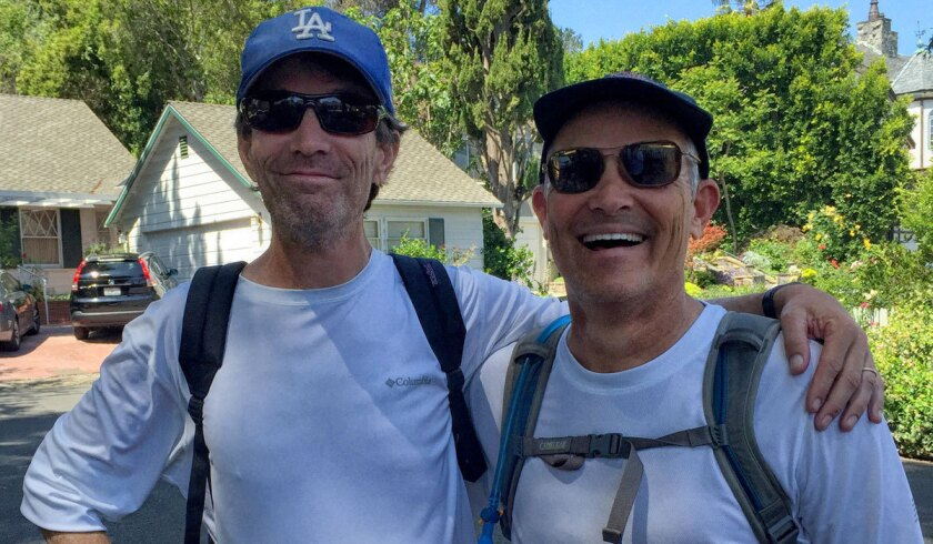 Rick Gottesman, left, and Jay Lewitt stop for a photo in Studio City on their way -- on foot -- to Dodger Stadium.