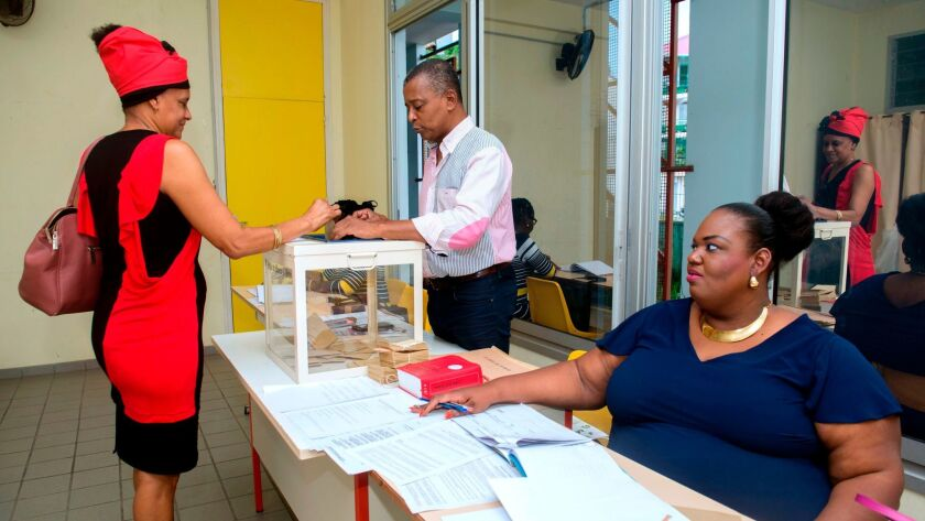 A woman casts her ballot during the second round of the French presidential election at a polling station on the French territory of Guadeloupe.