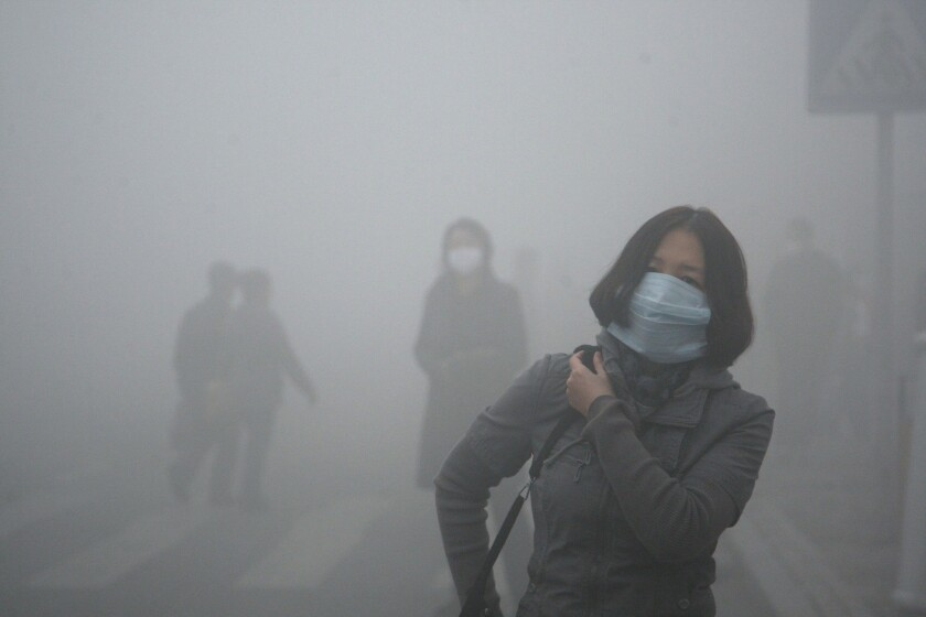 Pedestrians engulfed in thick air pollution wear masks in Harbin, China.