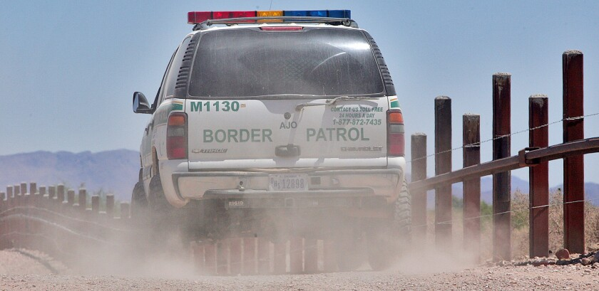 A U.S. Border Patrol agent patrols the border separating Sonoyta, Mexico, right of fence, and Lukeville, Ariz., on May 24, 2006.