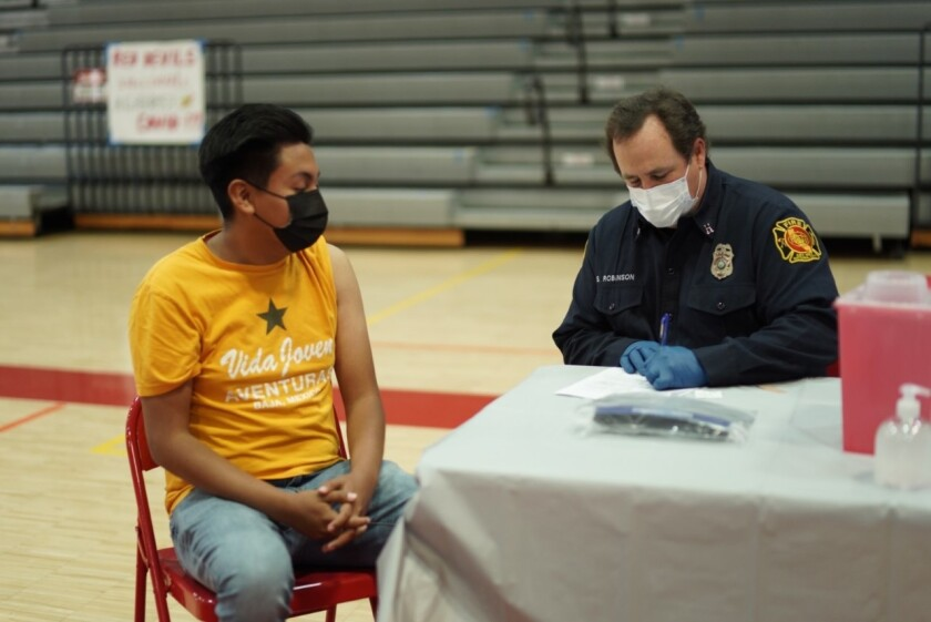 Student Kevin Andres prepares to receive a Pfizer vaccine at a vaccination site hosted by his school, Sweetwater High