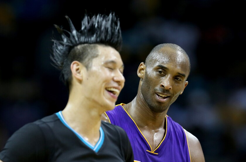 Lakers forward Kobe Bryant (24) talks to former teammate Jeremy Lin during a game against the Hornets.