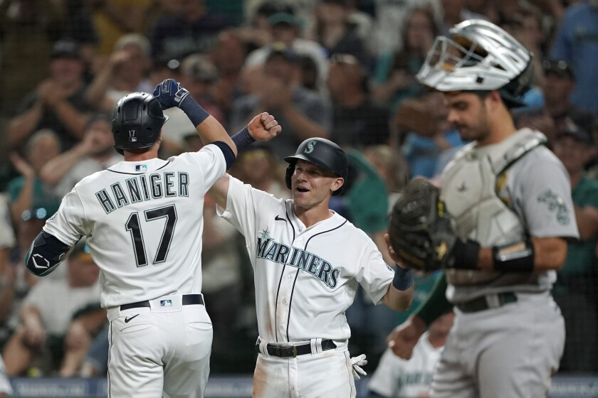 Seattle Mariners' Mitch Haniger (17) is greeted by Jake Bauers, center, after Haniger hit a two-run home run to score Bauers against the Oakland Athletics during the fifth inning of a baseball game Saturday, July 24, 2021, in Seattle. (AP Photo/Ted S. Warren)
