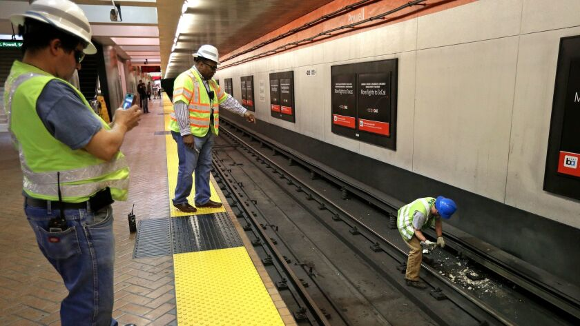 A BART worker destroys a faulty insulator with a sledgehammer at the Powell Street station in San Francisco.