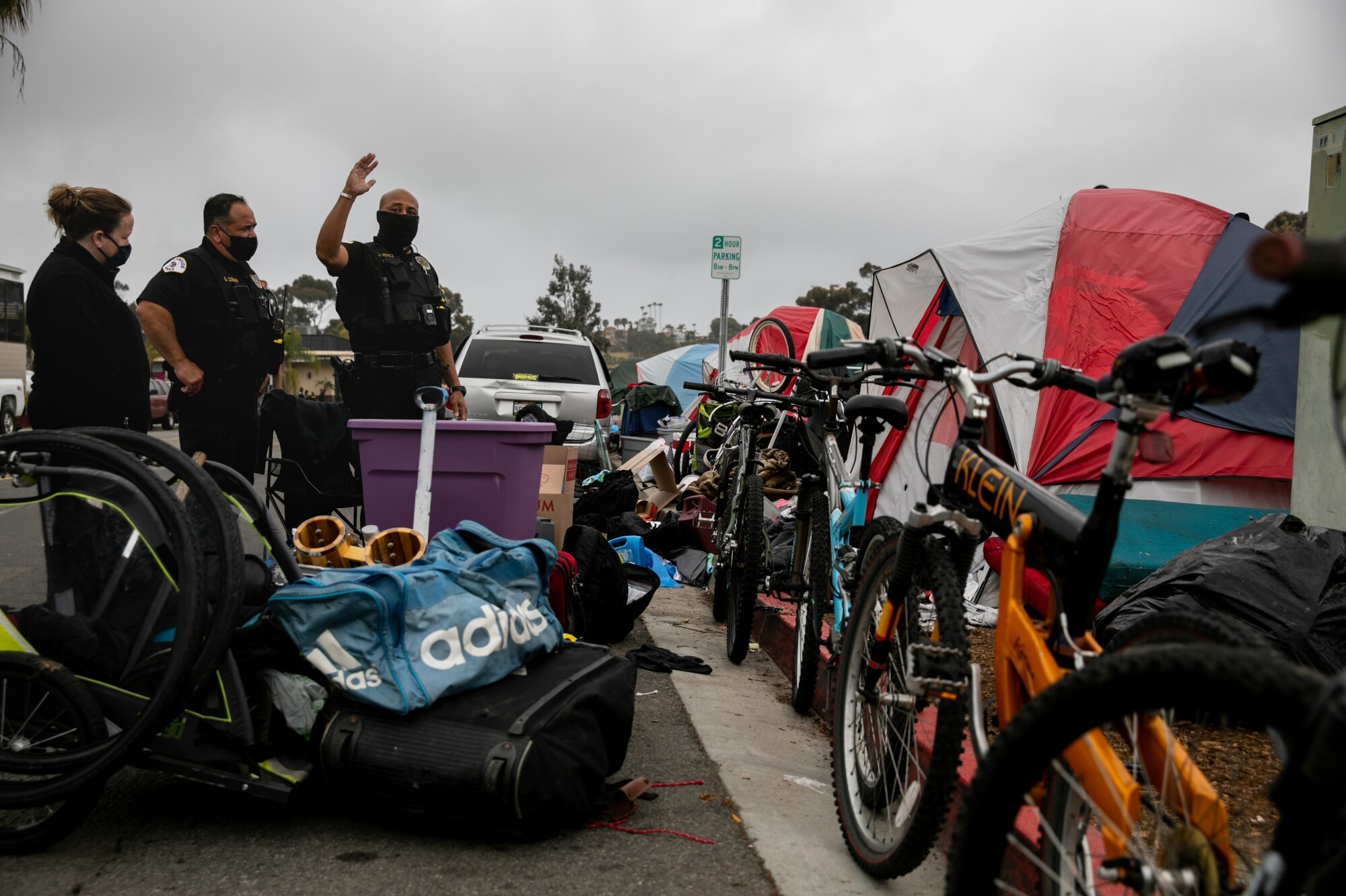 Oceanside police speak to Sean M. Kelley as they work to clear a homeless encampment near Oceanside Boulevard on Tuesday.