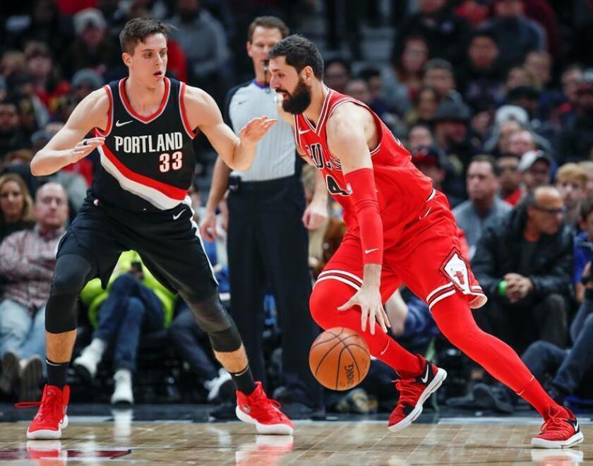 Nikola Mirotic (d) de Bulls disputa el balón ante Zach Collins (i) de Trail Blazers, durante el partido que este 1 de enero ha efrentado a ambos equipos en el United Center en Chicago, Illinois (EE.UU.). EFE